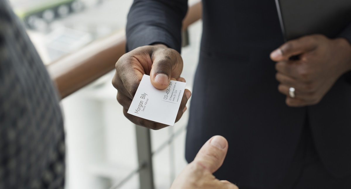 man handing business card
