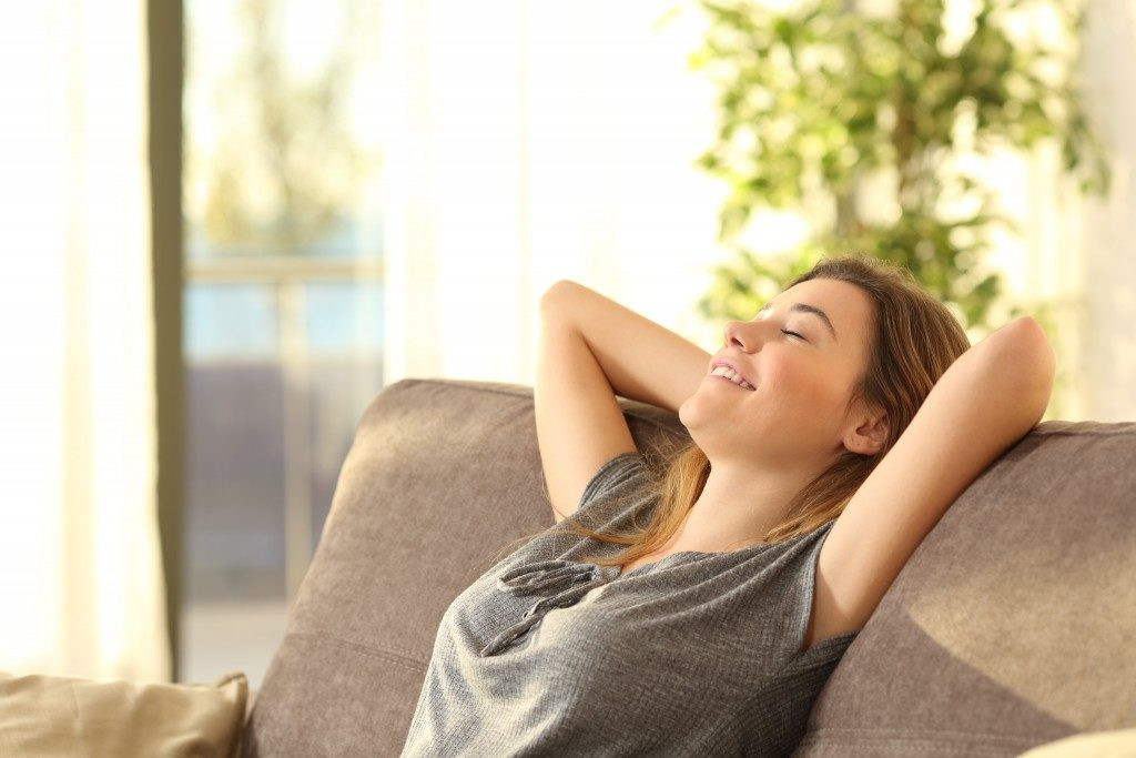 woman happily relaxing on her couch