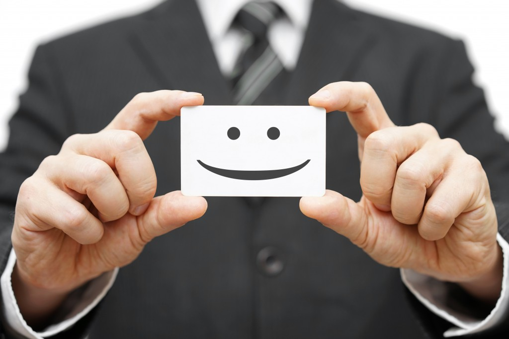 business man holding a card with happy face